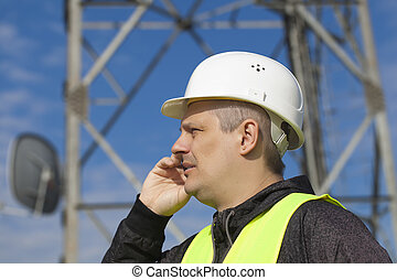 Engineer talking on the cell phone near to gsm towe