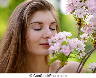 Young Beautiful Woman Smelling a Pink Sakura Flowers in the...