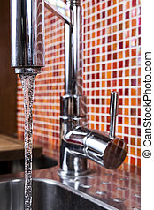 kitchen faucet flowing - closeup of water flowing from a...