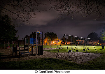 Eerie Childrens Playground at Night - A creepy scene of a...