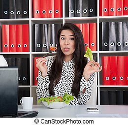 Business woman eating salad for lunch.