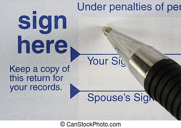 Sign Here - Income tax form with pen ready