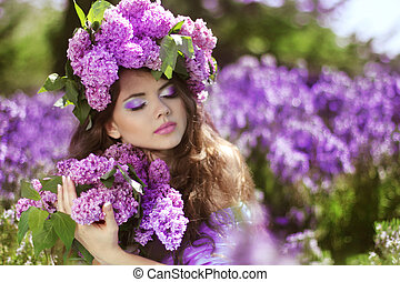 Beautiful young woman in lilac flowers, outdoors portrait