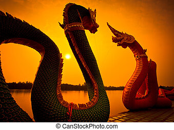 Silhouettes dragon and Naga statue protecting Thai temple
