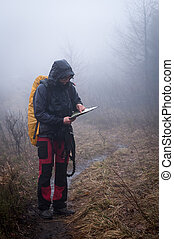 Lost in the mountains - Young woman reading a map in the...