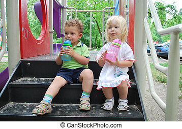 Friends - Boy and girl sitting on the sandbox and keep a...