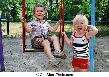 the girl shakes her boy on a swing - In the summer, bright...