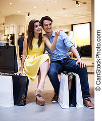 Beautiful couple resting after luxury shopping