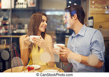 Two people in cafe enjoying the time spending with each...