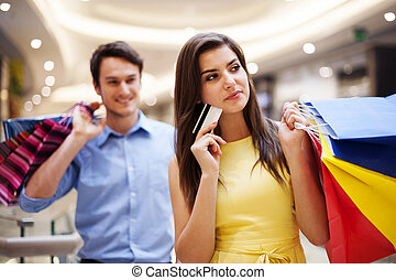 Focus young woman holding credit card and shopping bags