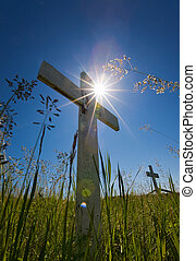 Grave sun flares - Old wooden crosses in a graveyard with...