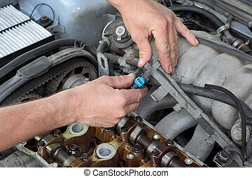 Automotive - Car mechanic fixing fuel injector at two...