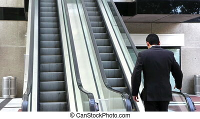 Confident businessman escalator