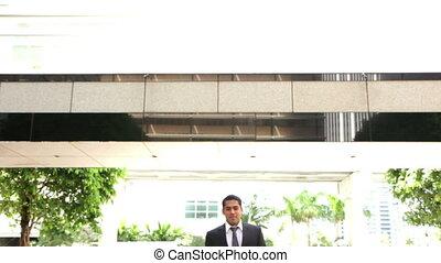 handsome businessman smiling - handsome businessman walking...