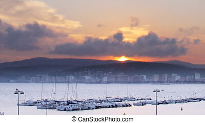 the sun setting over the harbour in the coastal town of palamos, costa brava, spain