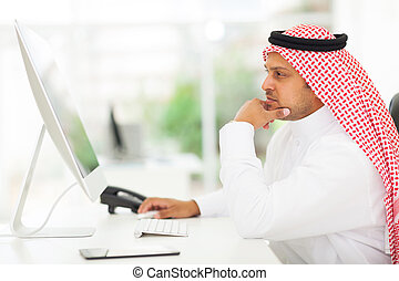 middle eastern businessman looking on a computer screen,...