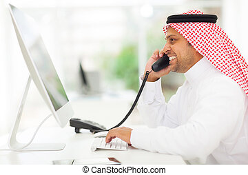 arabian businessman answering telephone - cheerful arabian...