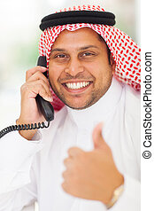 Arabic businessman talking on landline phone and giving...