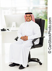 middle eastern businessman sitting in office - smiling...
