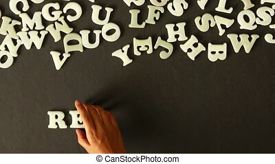 A person spelling Research with plastic letters.
