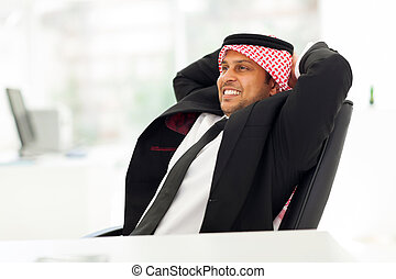 arab businessman relaxing in office - happy arab businessman...