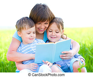 Family is reading book while sitting on a green grass...