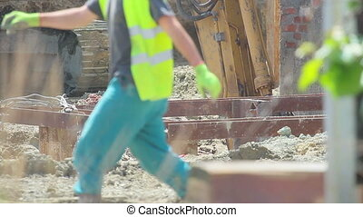Construction extravator diggin in the ground. People in the...
