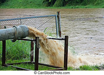 giant exhaust pipe pours into the muddy and Brown slurry