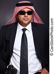 islamic bodyguard with a gun against black ground