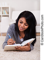 Young Woman Writing In Diary - Happy Young Woman Lying On...