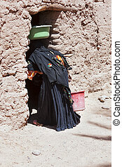 Berber, woman, entering, clay, house, M'hamid, Morocco
