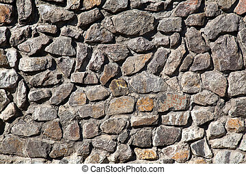 Old gray granite stone wall