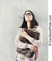 Thoughtful woman in eyeglasses holding bag Sad expression