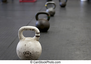 Kettlebells lined up on a gym floor