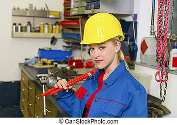 mechanic in workshop - young mechanic with yellow helmet and...