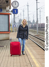 woman waiting for train station on their - a young woman...