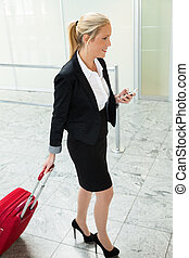 woman with suitcase and cell phone at the airport
