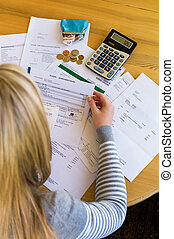 woman with debts and bills - a woman with unpaid bills has...