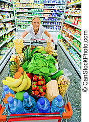 woman with shopping cart in supermarket - a woman when...