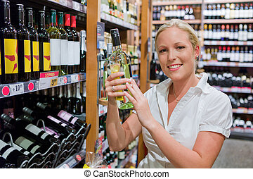 woman with wine shelf of a supermarket