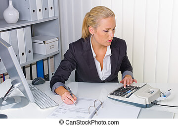 woman in office with calculator - an accountant at work in...