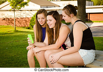 Pre-teen girls texting while hanging out in front of their...