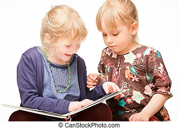 Children reading a book - Two cute little girls reading a...