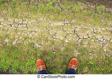 Orange boots on ground from above - Orange boots on patchy...