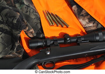 Hunting Season - Rifle and ammo on top of a hunting vest and...
