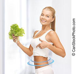 sporty woman with lettuce showing abs