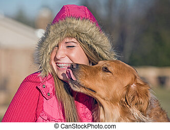 Dog Kissing Teenage Girl in Winter Clothes