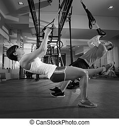 Fitness TRX training exercises at gym woman and man push-up...