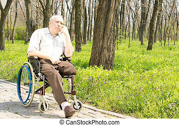 Pensive elderly amputee sitting alone on a rural pathway in...