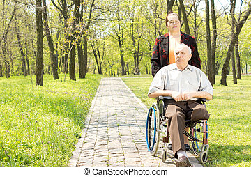Wife walking a disabled man in a wheelchair who has had one...